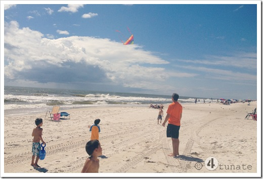 flying a kite at the beach with boys