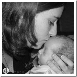mother kissing a preemie baby